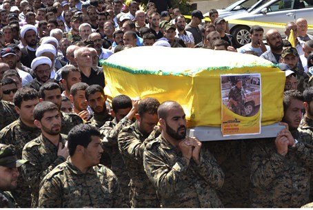 (Illustration) Hezbollah fighters carry coffi